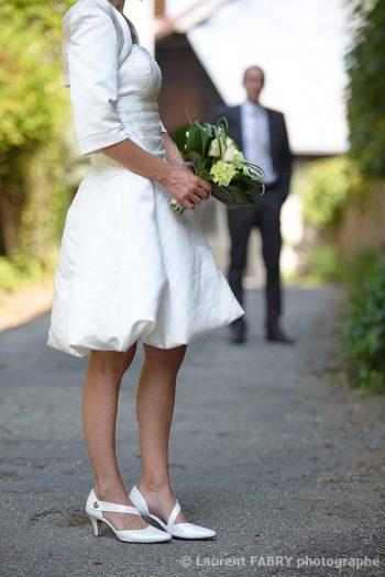détail de la robe et du bouquet de la mariée pendant sa séance photo de mariage près d