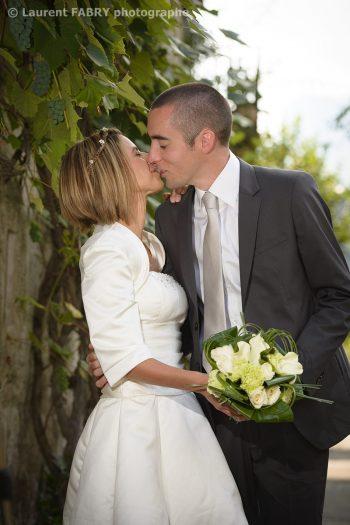 les mariés échangent un baiser dans une petite ruelle du village de Saint-Vital, mariage en Haute Combe de Savoie, 73