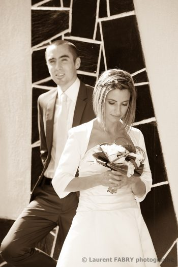 pose devant une architecture moderne en sépia pour ce couple avant le mariage dans un petit village de Savoie