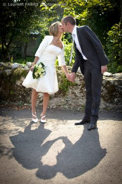 les mariés se donnent un baiser devant leur photographe de mariage