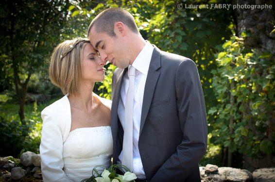 pose romantique des mariés sur fond de verdure suggérée par leur photographe de mariage