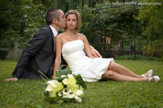 baiser des mariés assis dans l herbe devant le bouquet de mariage