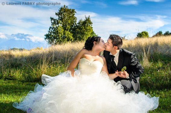 photo du baiser des mariés se tenant la main assis dans la nature