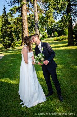 baiser des mariés tenant le bouquet de mariage dans un parc sous de grands arbres