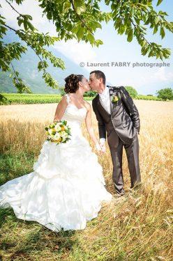 baiser champêtre des mariés au bord du champs de blé sous lachaleur d un bel été