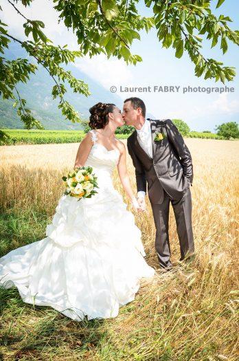 les mariés s embrassent devant un champ de blé en été dans la Combe de Savoie, mariage estival