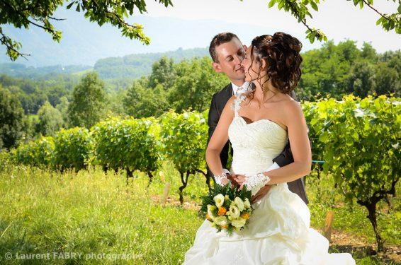les mariés posent pour leur photographe de mariage dans un décor ombragé du vignoble de Savoie
