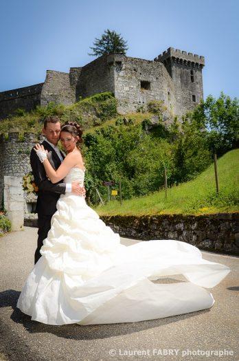les mariés posent pour leur photographe de mariage près du Château de Miolans, en Savoie