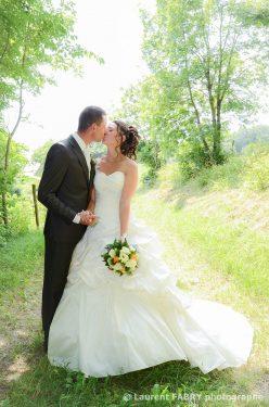 photo romantique de mariage : le baiser des mariés sur un chemin de montagne
