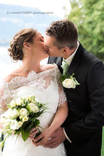 baiser des mariés, pose classique et romantique devant le lac du Bourget, à Bourdeaux, mariage dans les Alpes