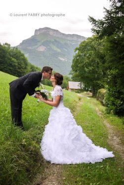 photo du baiser du marié sur fond de verdure et de montagne