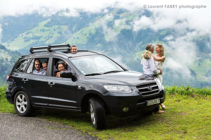 les mariés font leur séance photo devant un décor de montagne (mariage dans les Alpes)