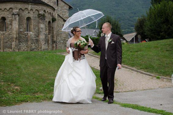 le marié apporte le parapluie à sa future épouse pendant la séance photo de couple