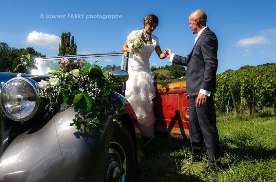 la mariée sort de la voiture sous l'œile regard attentif du photographe de mariage
