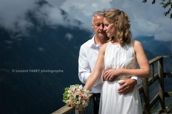 pose romantique des mariés sur fond de nature et de montagne