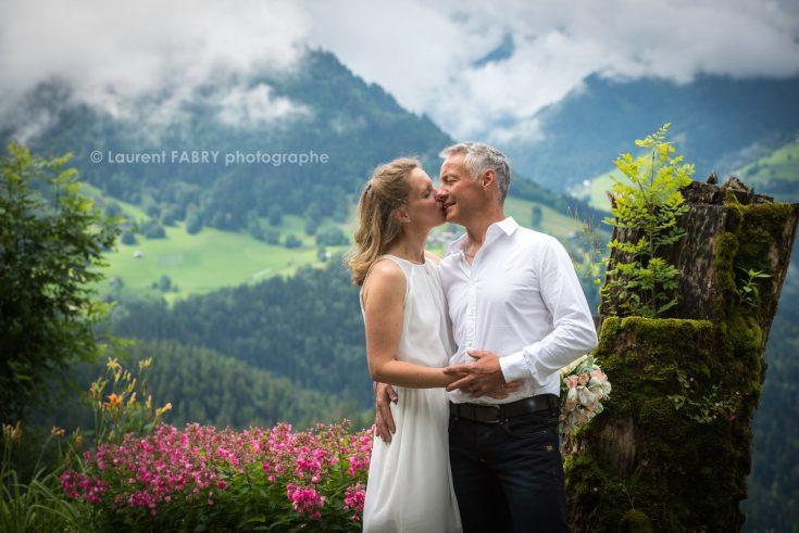 Baiser des mariés devant un décor de montagne fleuri au printemps (Beaufortain, Savoie) : mariage dans les Alpes