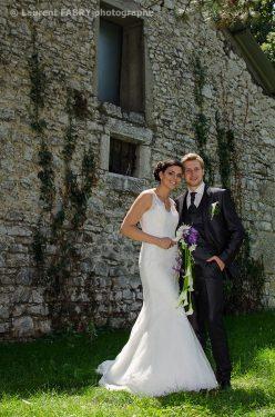 les mariés posent près du mur en pierre