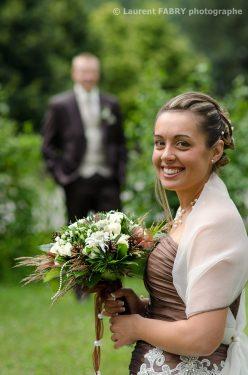 sourire de la mariée, avec son futur époux en arrière plan, photo en couleurs