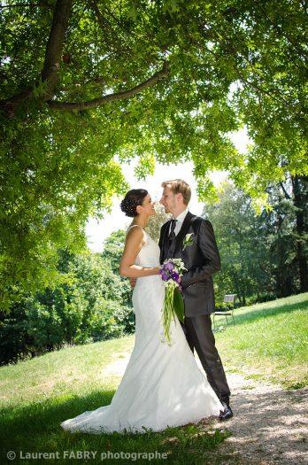 les mariés posent pour leur photographe dans un lieu ombragé au parc de Buisson Rond à Chambéry, Savoie
