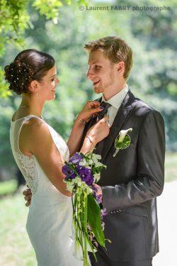la mariée ajuste la cravate du marié avant la cérémonie du mariage