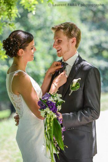 la mariée ajuste la cravate du marié dans le parc de Buisson Rond, avant la cérémonie du mariage à Chambéry, Savoie
