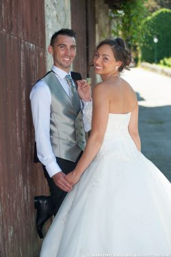 les mariés posent avec un sourir devant une porte de garage pour leur photographe