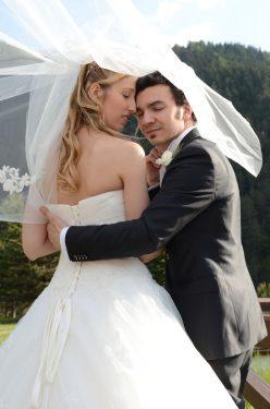 les mariés sous le voile de la mariée, yeux clos, posent pour leur photographe