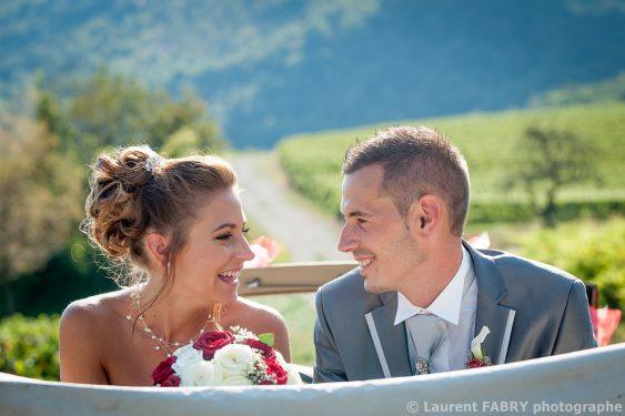les mariés échangent un regard et un sourir à l arrière de leur voiture