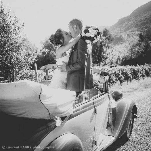 Baiser des mariés se tenant debout dans la voiture qui les conduira à la cérémonie (mariage à Saint-Pierre d Albigny, Savoie)