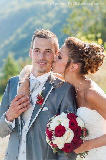 La mariée embrasse le marié sur la joue tout en tenant son bouquet à Saint-Pierre d Albigny, Savoie