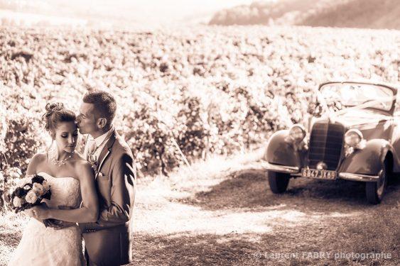 portrait des mariés dans les vignes avec la traction avant, photo sépia