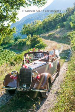 les mariés en promenade dans les chemins de montagne à bord de leur voiture traction avant