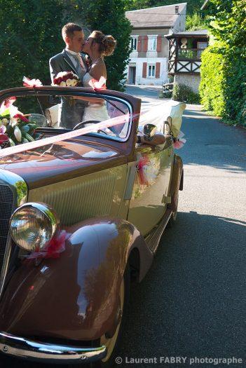 baiser des mariés debout à l arrière de leur leur voiture dans une ruelle de Saint-Pierre d Albigny