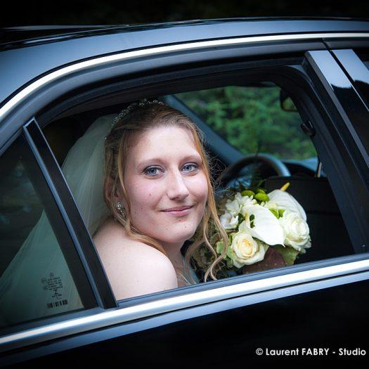 La mariée pose pour son photographe à l arrière de la voiture qui la conduira à la cérémonie - Bride posing for her photographer at the back of the car that will take her to the wedding ceremony