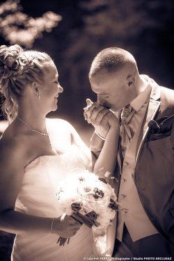 le marié embrasse la mariée sur la main, photographie sépia