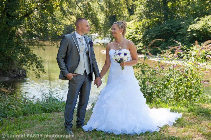les mariés posent devant le Guiers, une rivière entre Isère et Savoie lors de leur mariage