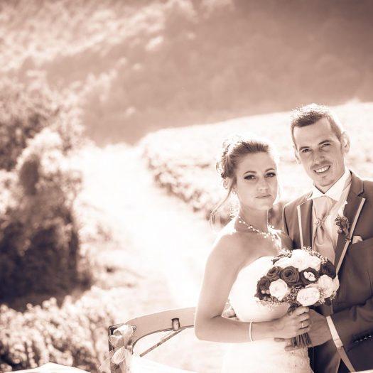 Sourire des mariés qui se tiennent debout dans leur voiture, traitement d image rose sépia - Smiling bride and groom, standing in their car, photo with a pink sepia effect