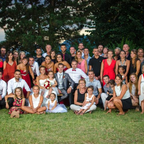 de nombreuses personnes se pressent autour des mariés en Combe de Savoie  pour une photo de groupe de mariage