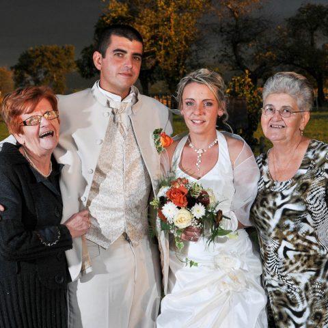 les mariés posent pour leur photographe avec des membres de leur famille en extérieur