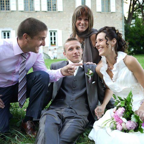 photos des mariés et leurs témoins assis sur le sol devant un château pendant leur vin d honneur