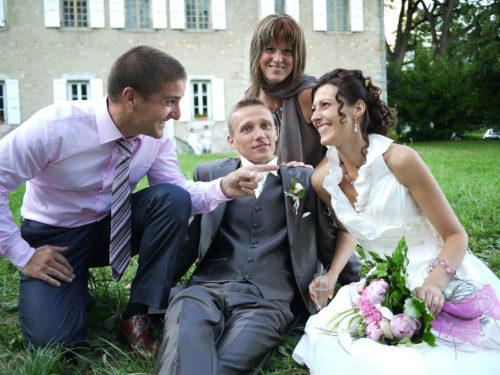 photos des mariés et leurs témoins assis sur le sol devant un château