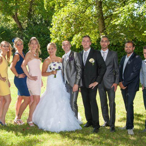 une photo de groupe avec hommes et femmes répartis de chaque côté des mariés