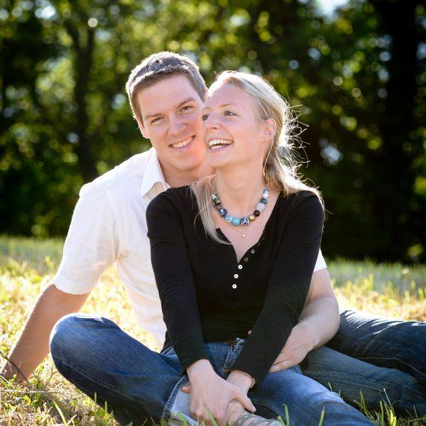 couple souriant assis au sol souriant lors de sa séance engagement avant le mariage en Combe de Savoie