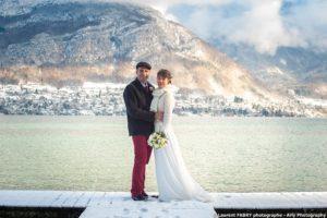 Laurent Fabry, photographe de mariage au bord du lac d'Annecy : portrait des mariés sur un ponton devant le paysage enneigé