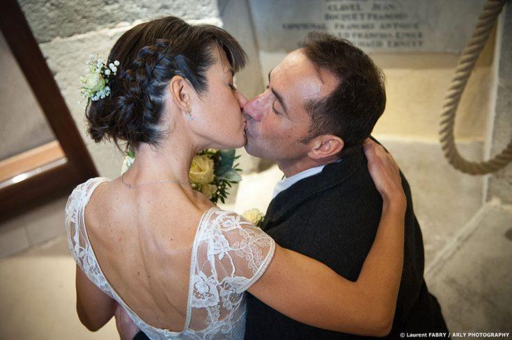 Baiser des mariés dans un escalier après leur cérémonie civile de mariage en mairie