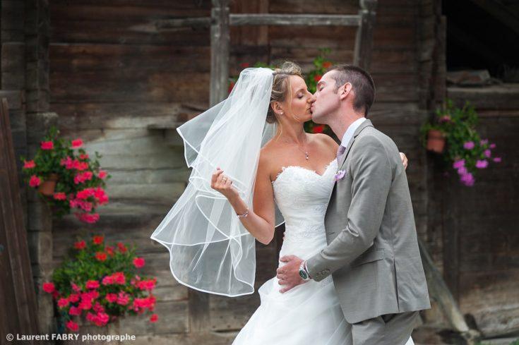 Photo des mariés devant un grenier fleuri en Savoie