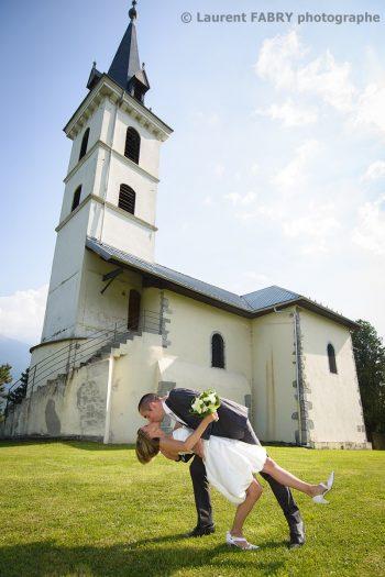 mariés photographiés devant une église pour leur mariage à Saint-Vital