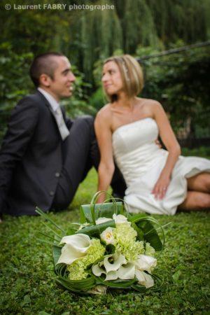 photo du bouquet devant les mariés assis dans leur jardin, mariage en Savoie
