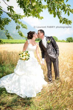 les mariés s embrassent devant un champ de blé en été dans la Combe de Savoie