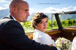 les mariés se rendent à leur mariage en Savoie dans une voiture cabriolet ancienne en compagnie de leur photographe